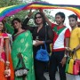 Image of a group of people of diferent cultures holding rainbow flags.