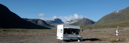 Image by Lise Autogena, of a trailer in the foreground of mountains.