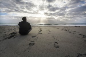 A man sitting on a beach looking at the sunset setting over the ocean. There are footprints in the sand around him.